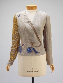 Veste de soirée (automne 1937) : Réalisée avec la collaboration de Jean Cocteau, cette veste de soirée en lin est brodée d'un personnage féminin représenté de profil. Alors que ses cheveux dorés s'échappent le long de la manche, son bras enserre délicatement la taille.